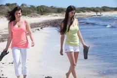 Γυναίκες στην παραλία που κρατά τις πτώσεις κτυπήματός τους Στοκ εικόνες με δικαίωμα ελεύθερης χρήσης