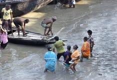 Γυναίκες στο λασπώδη ποταμό Ichamoti. Στοκ Φωτογραφία