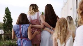 γυναίκες φιλίας s Το ξανθό κορίτσι στέκεται κοντά στα κιγκλιδώματα μπαλκονιών και κοιτάζει προς τα εμπρός Οι φίλες έρχονται σε τη φιλμ μικρού μήκους
