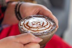 Γυναίκες χεριών με τον καφέ cappuccino σε ένα θολωμένο φλυτζάνι υπόβαθρο Στοκ Εικόνα