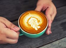 Γυναίκες χεριών με τον καφέ cappuccino σε ένα πράσινο φλυτζάνι σε ξύλινο Στοκ φωτογραφίες με δικαίωμα ελεύθερης χρήσης