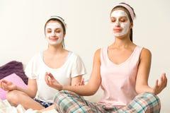 Γυναίκες Meditating που φορούν την άσπρη του προσώπου μάσκα Στοκ εικόνα με δικαίωμα ελεύθερης χρήσης