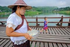 Γυναίκες Mon στο περπάτημα στην ξύλινη γέφυρα που διασχίζει την τεχνητή λίμνη khao laem Στοκ εικόνα με δικαίωμα ελεύθερης χρήσης