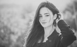 Γυναίκες ` s hairstyle μοντέρνη θέτοντας γυναίκα Μακριά τρίχα brunette αφής κοριτσιών στο φυσικό τοπίο Στοκ Φωτογραφίες