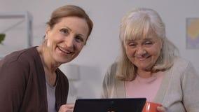 Γυναίκες Senor που αντιμετωπίζουν εύκολα app στην ταμπλέτα και που εξετάζουν τη κάμερα, τεχνολογίες απόθεμα βίντεο