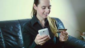 Γυναικεία αγορά on-line με μια πιστωτική κάρτα και μια έξυπνη τηλεφωνική συνεδρίαση σε έναν καναπέ στο σπίτι με ένα θολωμένο υπόβ φιλμ μικρού μήκους