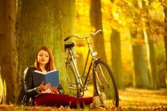 Γυναικεία ανάγνωση κάτω από το δέντρο Στοκ Εικόνα