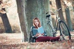 Γυναικεία ανάγνωση κάτω από το δέντρο Στοκ Φωτογραφία