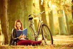Γυναικεία ανάγνωση κάτω από το δέντρο Στοκ Εικόνες