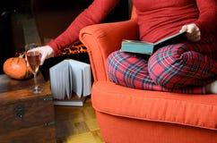 Γυναικεία ανάγνωση και χαλάρωση από την εστία Στοκ Εικόνες