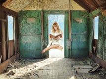 Γυναικεία ανάγνωση Levitating στο χαμόσπιτο Στοκ Φωτογραφίες