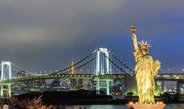 Γυναικεία αντιπαραβαλλόμενη ελευθερία στάση στη γέφυρα Odaiba και ουράνιων τόξων Στοκ Φωτογραφίες