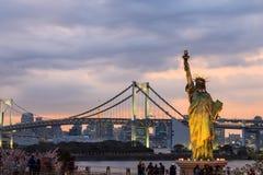 Γυναικεία αντιπαραβαλλόμενη ελευθερία στάση στη γέφυρα Odaiba και ουράνιων τόξων Στοκ εικόνες με δικαίωμα ελεύθερης χρήσης