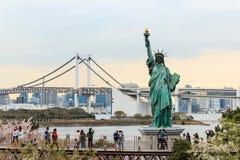 Γυναικεία αντιπαραβαλλόμενη ελευθερία στάση στη γέφυρα Odaiba και ουράνιων τόξων Στοκ φωτογραφία με δικαίωμα ελεύθερης χρήσης