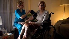Γυναικεία νοσοκόμα που μετρά τη πίεση του αίματος γυναικών, υπέρταση, απόγνωση μεγάλης ηλικίας στοκ εικόνες