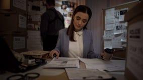 Γυναικεία σπόλα με τον καφέ που εξετάζει την περίπτωση, που διαβάζει τις δηλώσεις μάρτυρα, κατάλογος στοιχείων στοκ φωτογραφίες