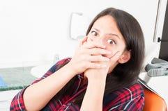 Γυναικεία συνεδρίαση στην καρέκλα οδοντιάτρων που καλύπτει το στόμα της Στοκ Φωτογραφίες