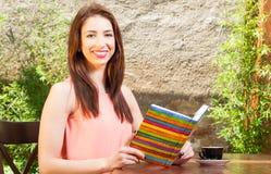 Γυναικεία συνεδρίαση χαμόγελου στο χρωματισμένο εκμετάλλευση σημειωματάριο πεζουλιών Στοκ Φωτογραφία