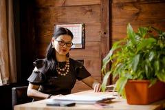 Γυναικεία συνεδρίαση Brunnette στο ξύλινο γραφείο στο γραφείο Στοκ Εικόνες