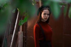 Γυναικεία τοποθέτηση σε ένα σκούρο κόκκινο υπόβαθρο Η πρότυπη φθορά μοντέρνη ευρύς-το καπέλο Το κορίτσι εξετάζει τη κάμερα Θηλυκή Στοκ Εικόνες