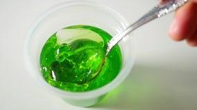 Γυναικεία χέρια που χρησιμοποιούν το κουτάλι για να εκσκάψει την πράσινη ζελατίνα να δειπνήσει στον πίνακα σε σε αργή κίνηση φιλμ μικρού μήκους