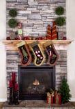 Γυναικείες κάλτσες Χριστουγέννων που κρεμούν από την εστία Στοκ Φωτογραφία