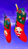 Γυναικείες κάλτσες και δώρα Χριστουγέννων που κρεμούν στο σχοινί στο υπόβαθρο ουρανού Στοκ Εικόνες