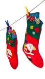 Γυναικείες κάλτσες και δώρα Χριστουγέννων που κρεμούν στο σχοινί Στοκ Εικόνες