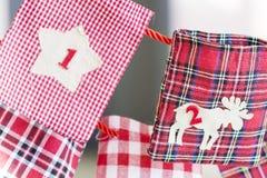 Γυναικείες κάλτσες Χριστουγέννων για τα δώρα που κρεμούν στο κόκκινο σχοινί - κλείστε επάνω Στοκ Φωτογραφία
