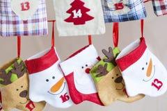 Γυναικείες κάλτσες Χριστουγέννων για τα δώρα που κρεμούν στο κόκκινο σχοινί - κλείστε επάνω Στοκ Εικόνες