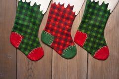 Γυναικείες κάλτσες Χριστουγέννων που κρεμούν ενάντια στον ξύλινο τοίχο Στοκ εικόνες με δικαίωμα ελεύθερης χρήσης