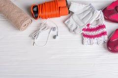 Γυναικείος αθλητισμός που τίθεται σε ένα άσπρο ξύλινο υπόβαθρο με ένα σχοινί για το άλμα Στοκ Φωτογραφία