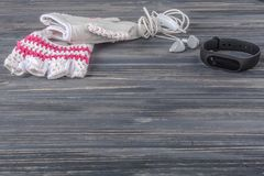 Γυναικείος αθλητισμός που τίθεται σε ένα γκρίζο ξύλινο υπόβαθρο με ένα βραχιόλι ικανότητας Στοκ φωτογραφία με δικαίωμα ελεύθερης χρήσης