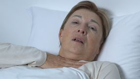 Γυναικείος ασθενής που αναπνέει μετά βίας στο νοσοκομειακό κρεβάτι, χέρι τεντώματος για τη βοήθεια, άσθμα απόθεμα βίντεο