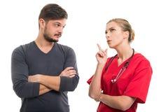 Γυναικείος γιατρός που εξηγεί κάτι στον αρσενικό ασθενή Στοκ Εικόνες