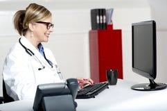 Γυναικείος γιατρός που εργάζεται στον υπολογιστή Στοκ Φωτογραφία