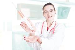 Γυναικείος γιατρός που παρουσιάζει μεγάλη σύριγγα Στοκ εικόνα με δικαίωμα ελεύθερης χρήσης