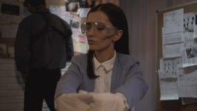 Γυναικείος εγκληματολόγος στα γάντια που κρατά τα στοιχεία σφαιρών στη πλαστική τσάντα, πείρα φιλμ μικρού μήκους