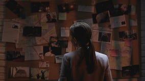 Γυναικείος ιδιωτικός πράκτορας που εξετάζει τον πίνακα έρευνας εγκλήματος, φλιτζάνι του καφέ κατανάλωσης απόθεμα βίντεο