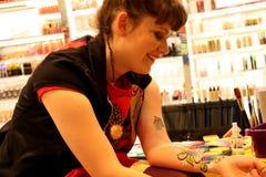 Γυναικείος καλλιτέχνης της ζωηρόχρωμης ζωγραφικής σε ένα δέρμα ή Facepainting με τη βούρτσα Στοκ φωτογραφίες με δικαίωμα ελεύθερης χρήσης