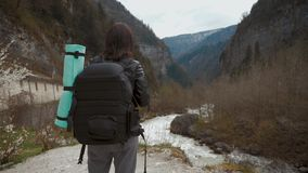 Γυναικείος οδοιπόρος με το σακίδιο πλάτης που κοιτάζει στους λόφους και τη λίμνη ποταμών βουνών, κορίτσι που απολαμβάνει το πανορ φιλμ μικρού μήκους