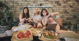 Γυναικείος πολυ εθνικός εφήβων επιταχύνοντας έναν φιλικό χρόνο μαζί σε ένα σύγχρονο παιχνίδι κρεβατοκάμαρων σε ένα PlayStation κα απόθεμα βίντεο