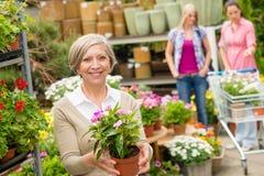 γυναικείος σε δοχείο πρεσβύτερος λαβής κήπων κεντρικών λουλουδιών Στοκ Εικόνες