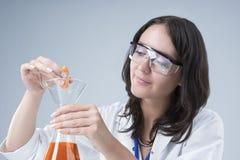 Γυναικείο προσωπικό που εξετάζει το δείγμα της Apple και το υγρό δοκιμής στη φιάλη Στοκ Φωτογραφίες