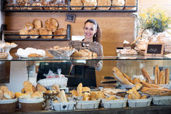 Γυναικείο προσωπικό που πωλεί τη φρέσκα ζύμη και τα baguettes στοκ εικόνα