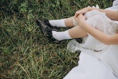 Γυναικών αγροτών συνεδρίασης μαύρα παπούτσια φορεμάτων χλόης άσπρα στοκ φωτογραφίες