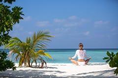 Γυναικών γιόγκας περισυλλογής στη γαλήνια τροπική παραλία Η χαλάρωση κοριτσιών στο λωτό θέτει στην ήρεμη στιγμή zen στο ωκεάνιο ν Στοκ Εικόνες