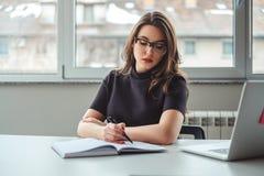 Γυναικών στο σημειωματάριό της στο γραφείο στοκ φωτογραφία με δικαίωμα ελεύθερης χρήσης