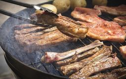 Γυρίζοντας το νόστιμο καρυκευμένο κρέας που μαγειρεύεται σε ένα braai ή μια σχάρα στοκ εικόνες