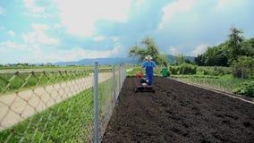 Γυρίζοντας το χώμα γύρω με το μικρής κλίμακας καλλιεργητή φιλμ μικρού μήκους